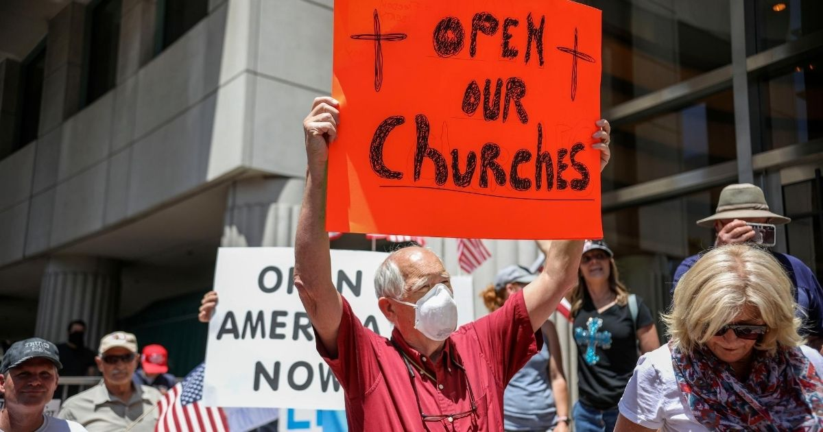 Demonstrators hold signs during a rally to reopen California on May 1, 2020, in San Diego, California.