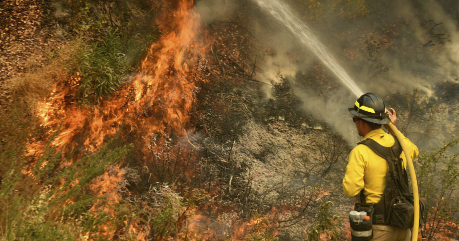 A firefighter puts out a fire northwest of Forrest Falls, California, on Sept. 10, 2020.