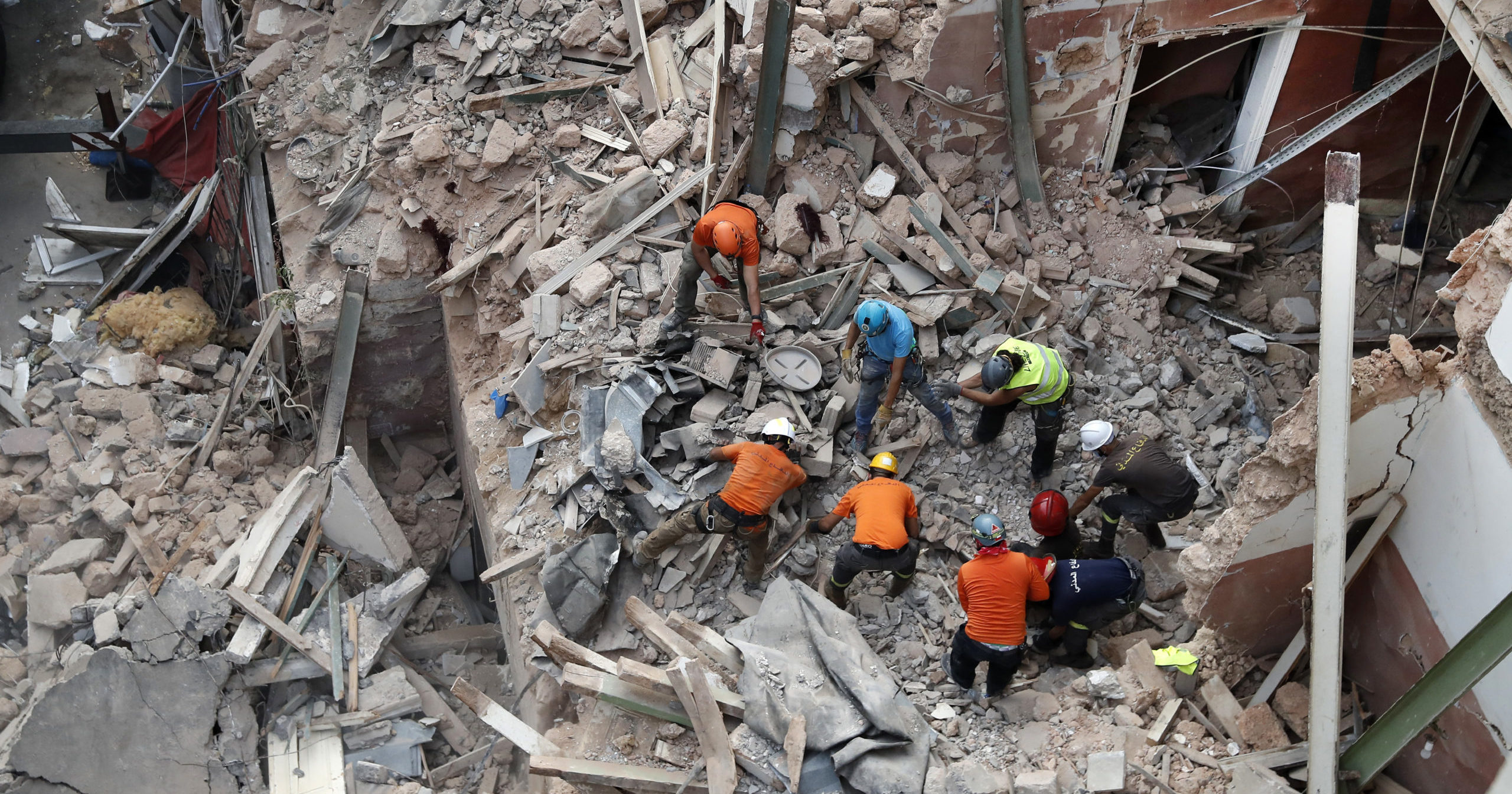 Lebanese and Chilean rescuers search in the rubble of a collapsed building after getting signals of a possible survivor on Sep. 4, 2020, in Beirut, Lebanon. A pulsing signal was detected from under the rubble of a Beirut building that collapsed during the horrific port explosion in the Lebanese capital last month, raising hopes there may be a survivor still buried there.