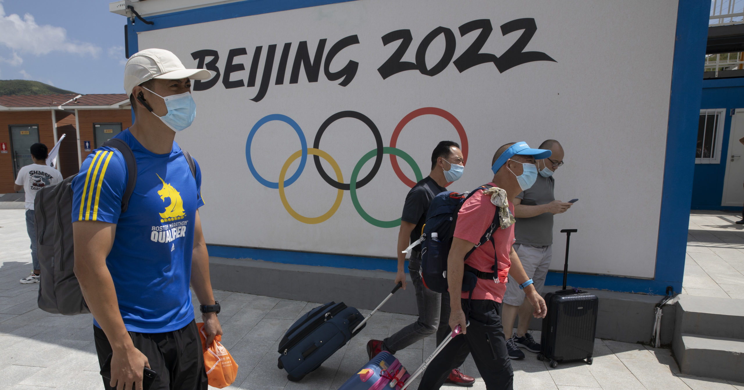 Visitors to Chongli, one of the venues for the Beijing 2022 Winter Olympics, walk by the Olympics logo on Aug. 13, 2020. China is host to the 2022 Winter Olympics with rumblings of a boycott and calls to remove the games from Beijing because of widespread human rights violations.