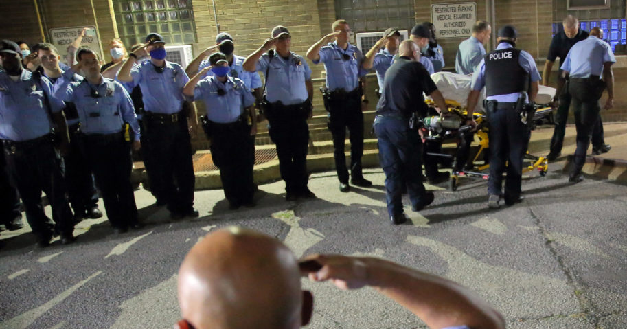 St. Louis police officers line up and salute as the body of fallen officer Tamarris L. Bohannon is brought to the morgue in St. Louis on Aug. 30, 2020. Bohannon died after being shot in the head by a barricaded gunman on the city's south side, authorities said.