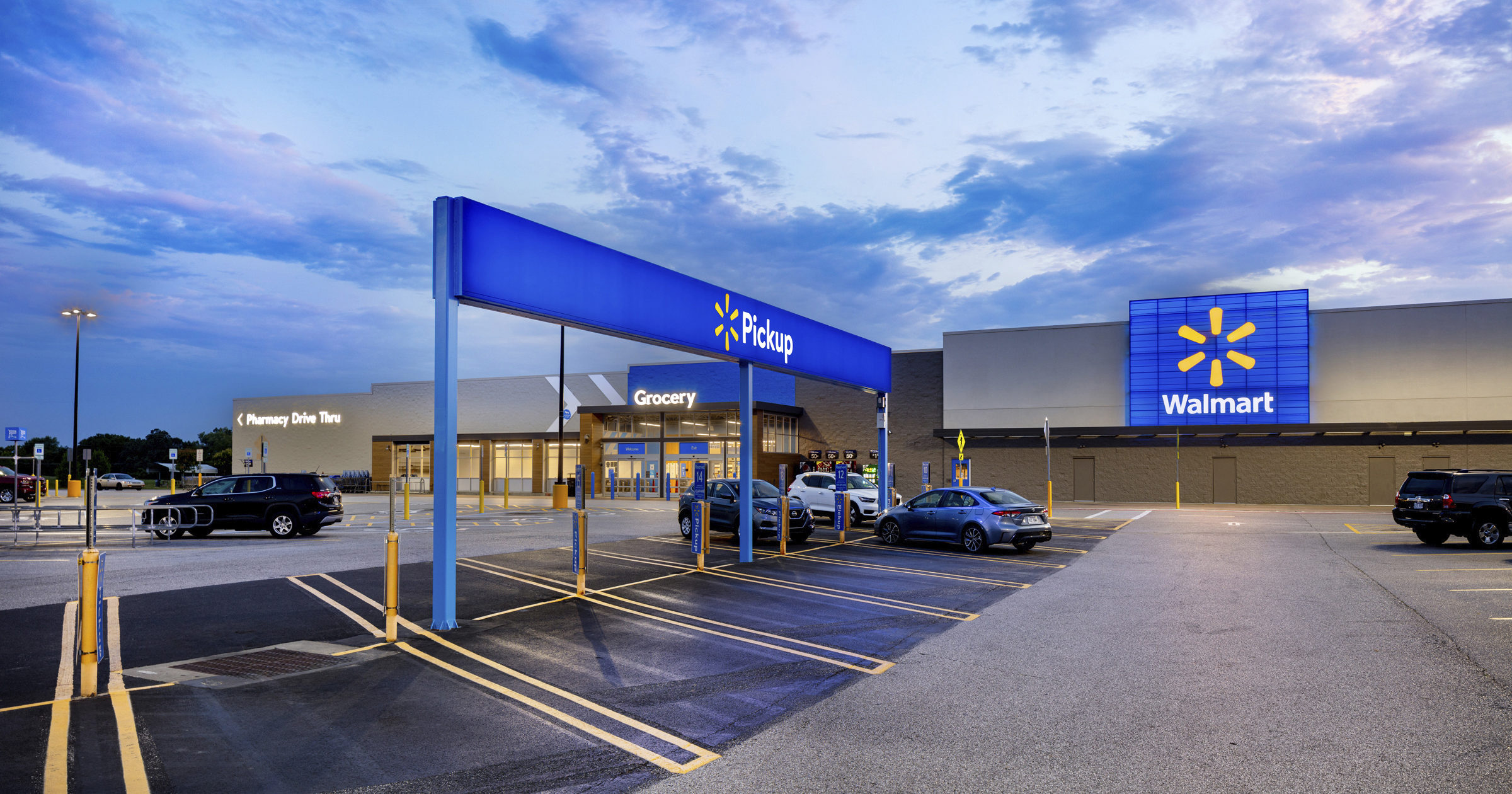 This July 2020 photo provided by Walmart shows the bright signage and Walmart logos from the parking lot outside the Walmart Supercenter in Springdale, Arkansas. Walmart is getting inspiration from the airport terminal as it revamps the layout and signage of its stores to speed up shopping and better cater to smartphone-armed customers.