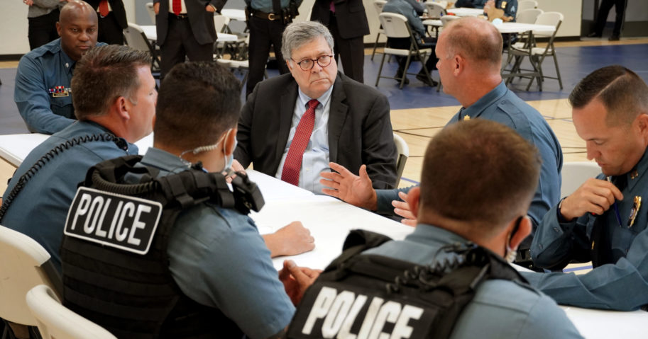 In this Aug. 19, 2020, photo, Attorney General William Barr speaks with police officers from the Kansas City Police Department in Kansas City, Missouri.