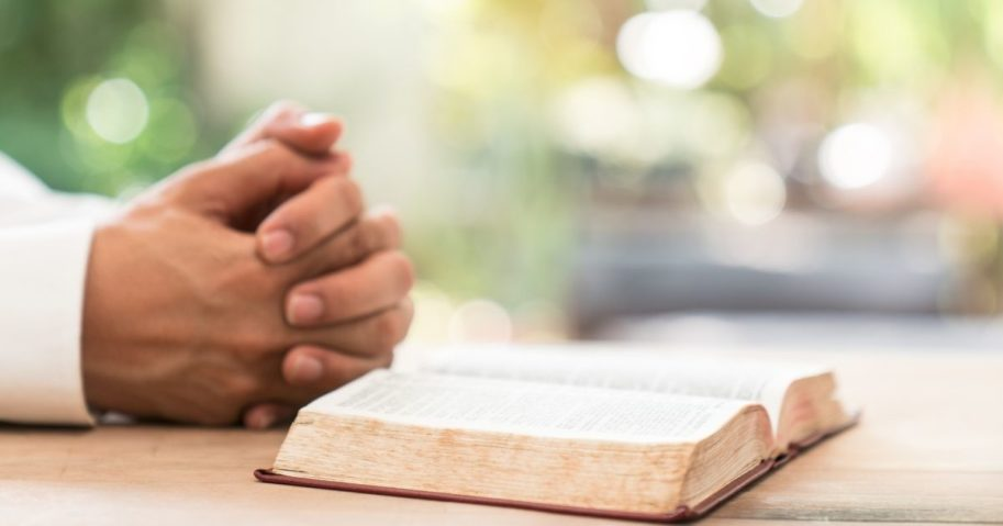 A man prays next to a Bible in the stock image above.