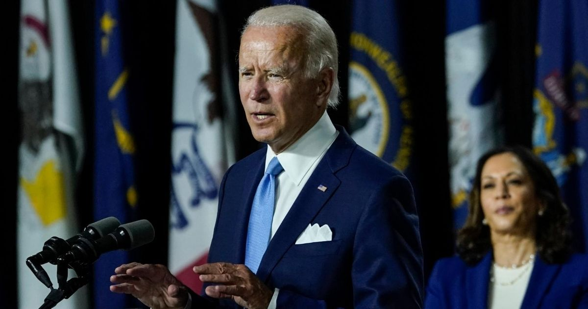 Democratic presidential nominee Joe Biden speaks as his running mate Sen. Kamala Harris looks on during an event at the Alexis Dupont High School in Wilmington, Delaware, on Aug. 12, 2020.