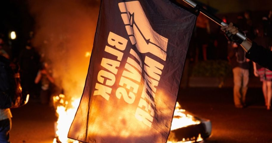 A Black Lives Matter flag waves in front of a fire at the North Precinct Police building in Portland, Oregon, on Sept. 6, 2020.