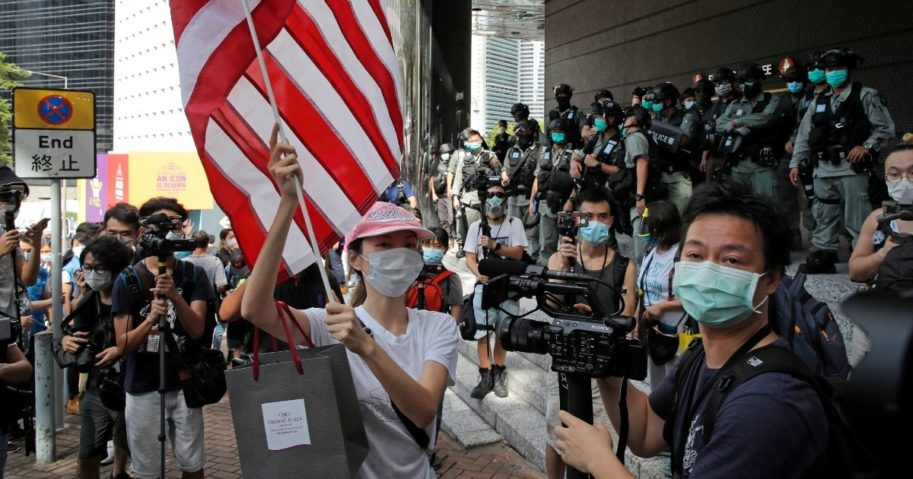 "A woman carries an American flag during a protest outside the U.S. Consulate in Hong Kong. The U.S. has issued a new advisory Tuesday, Sept. 15, 2020, warning against travel to mainland China and Hong Kong, citing the risk of ""arbitrary detention"" and 'arbitrary enforcement of local laws.'"