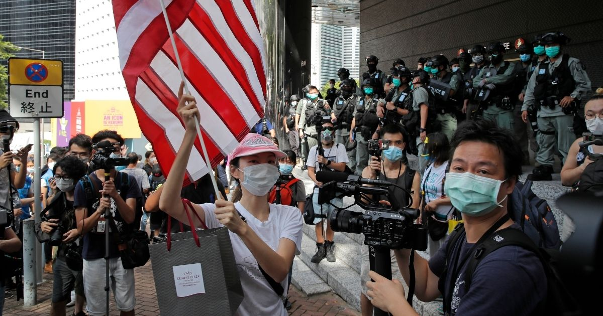 """A woman carries an American flag during a protest outside the U.S. Consulate in Hong Kong. The U.S. has issued a new advisory Tuesday, Sept. 15, 2020, warning against travel to mainland China and Hong Kong, citing the risk of """"arbitrary detention"""" and 'arbitrary enforcement of local laws.'"""