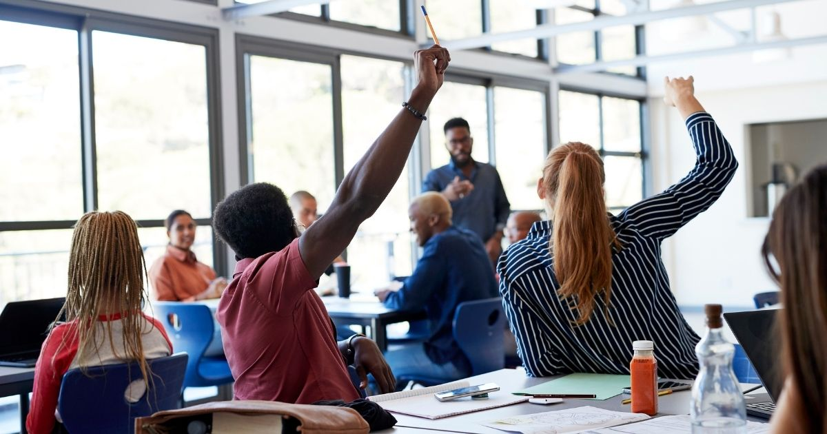 Students raise their hands at their desks in the above stock photo.