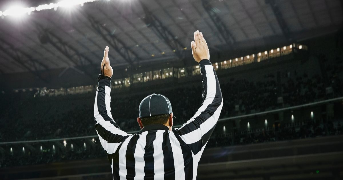 A football referee signals a touchdown in the stock image above.