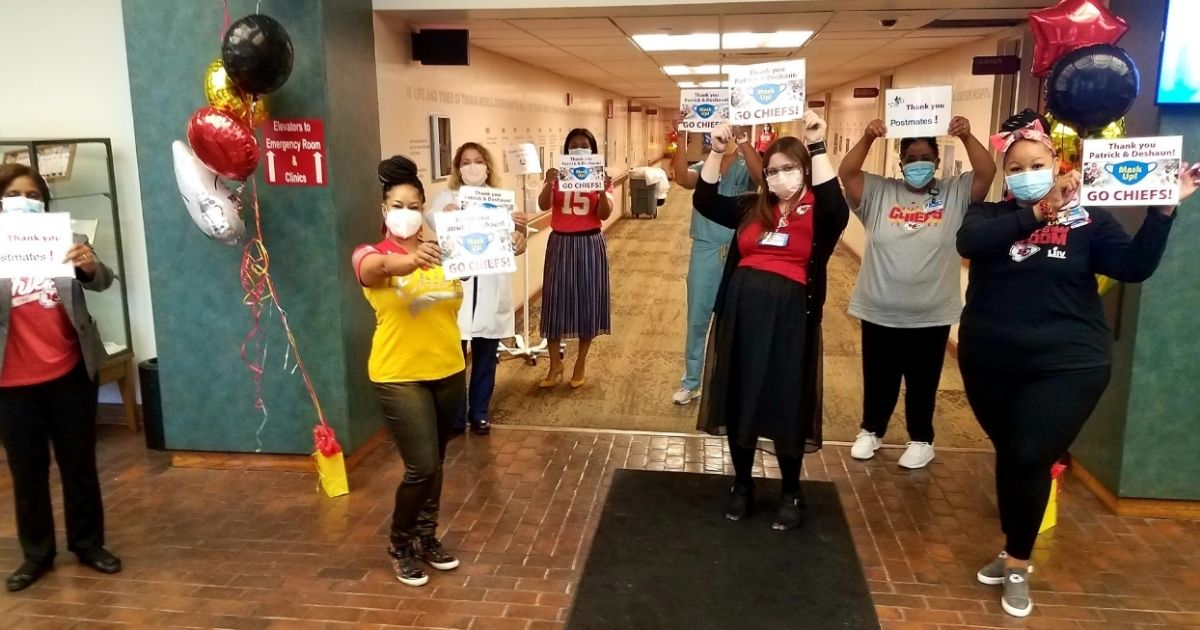 """Truman Medical Center front-line workers and recipients of donated meals from Deshaun Watson hold up signs that say """"Go Chiefs!"""""""