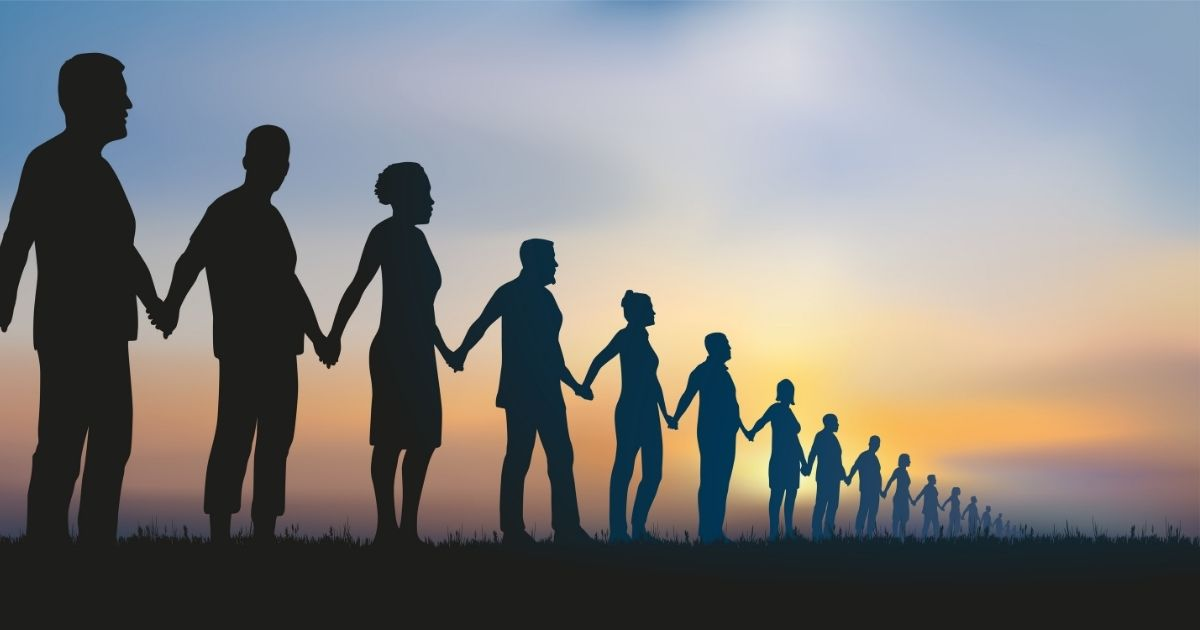 A group of people stand together as a human chain in the above stock photo.
