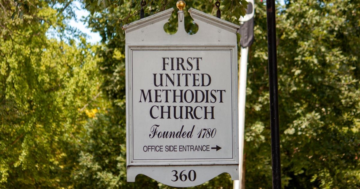 A wooden board sign points to the First United Methodist Church in downtown Chestertown, Maryland.