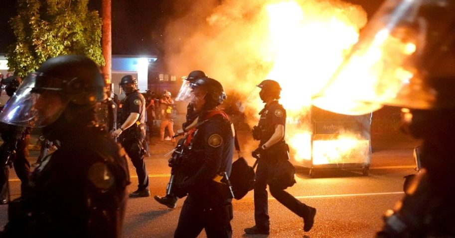 Portland police walk past a dumpster fire during a crowd dispersal on Aug. 14, 2020, in Portland, Oregon.