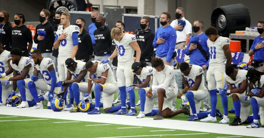 Jared Goff, left,, Cooper Kupp, center, and Josh Reynolds of the Los Angeles Rams stand while their teammates kneel in protest during the national anthem before their game against the Dallas Cowboys at SoFi Stadium in Inglewood, California on Sept. 13, 2020.