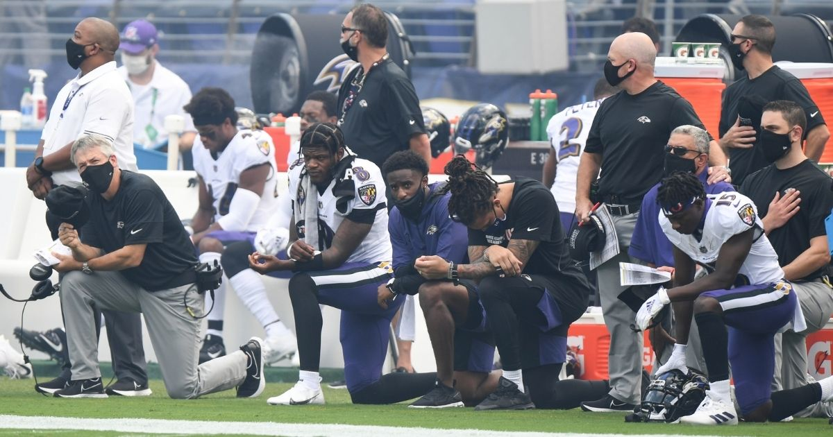 Baltimore Ravens players, including reigning NFL MVP Lamar Jackson (No. 8), kneel in protest during the national anthem before their game against the Cleveland Browns at M&T Bank Stadium on Sept. 13, 2020.