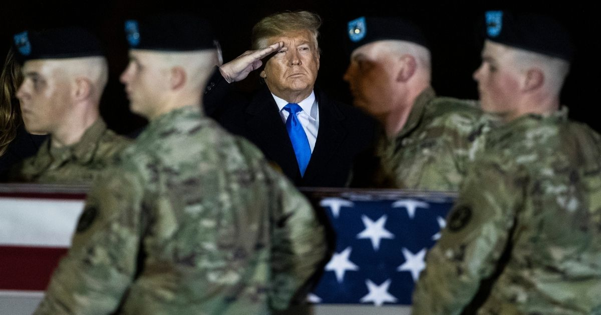 President Donald Trump watches as an Army carry team moves a transfer case containing the remains of Chief Warrant Officer 2 David C. Knadle of Tarrant, Texas, on Nov. 21, 2019, at Dover Air Force Base, Delaware.