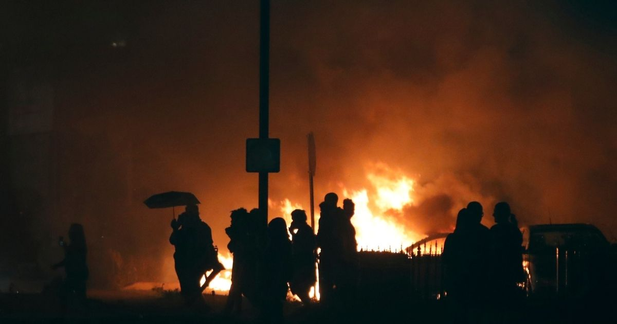 The silhouettes of the demonstrators outline against the glowing flames of cars they set on fire a few blocks from the County Court House during a demonstration against the shooting of Jacob Blake, who was shot in the back multiple times by police the day before, prompting community protests in Kenosha, Wisconsin, on Aug. 24, 2020.