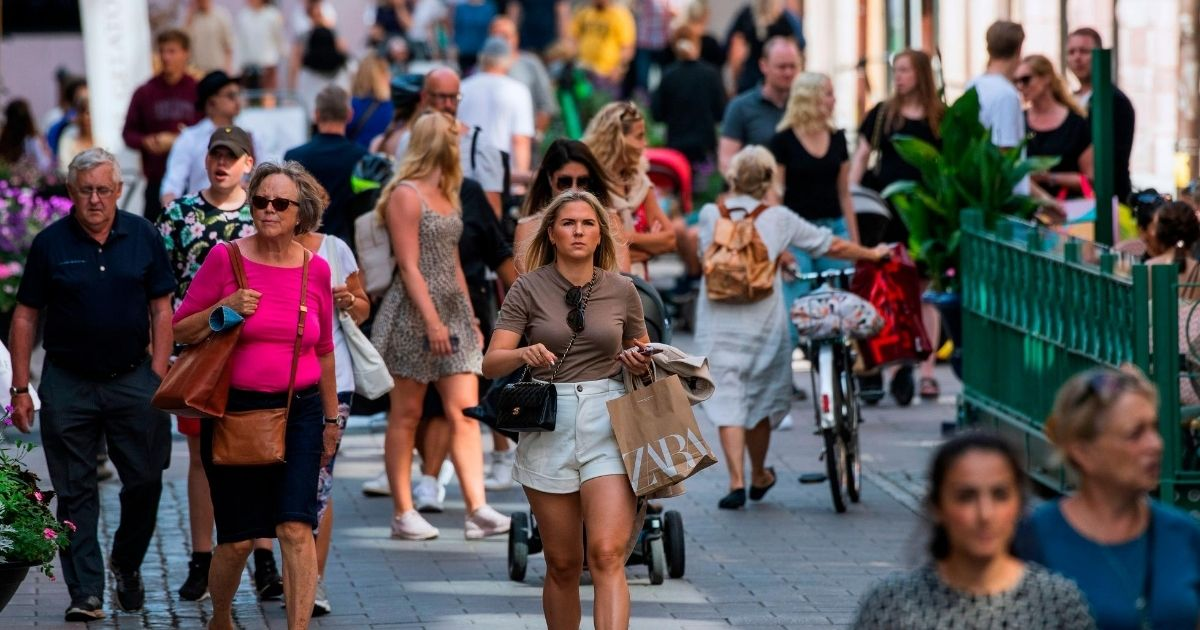 People walk down a street in Stockholm on July 27, 2020, during the coronavirus pandemic.