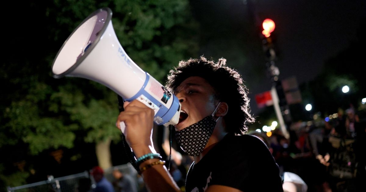 A protester yells into a megaphone during a protest on the fourth night of the Republican National Convention on Aug. 27, 2020, in Washington, D.C.