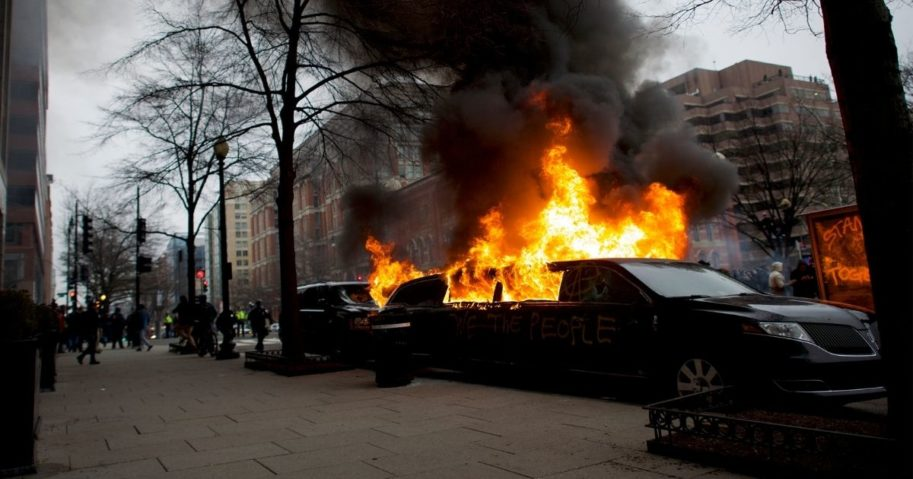 "A limousine is set aflame with ""We the People"" spray-painted on the side after the inauguration of Donald Trump as the 45th president of the United States Jan. 20, 2016, in Washington, D.C."