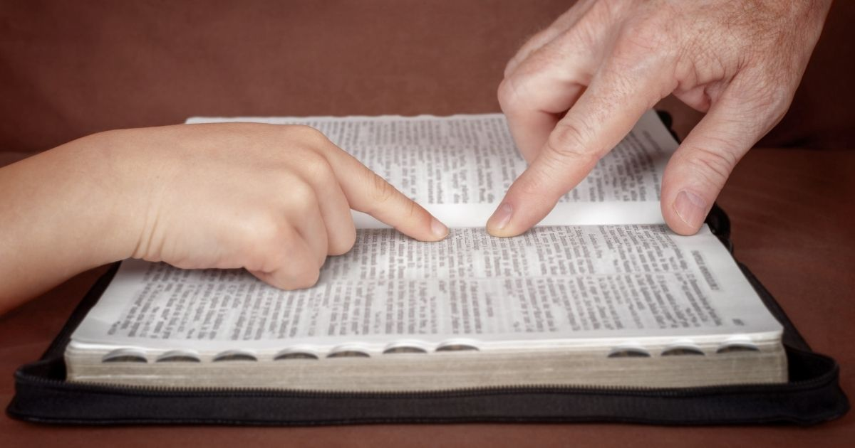 Two people studying the Bible are pictured in the stock image above.