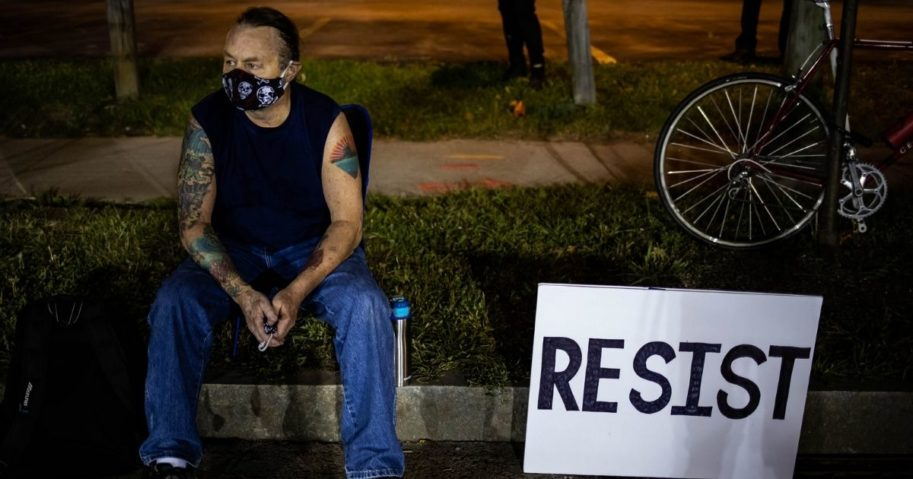 A protester sits during the sixth consecutive night of protests on Sept. 7, 2020, in Rochester, New York.