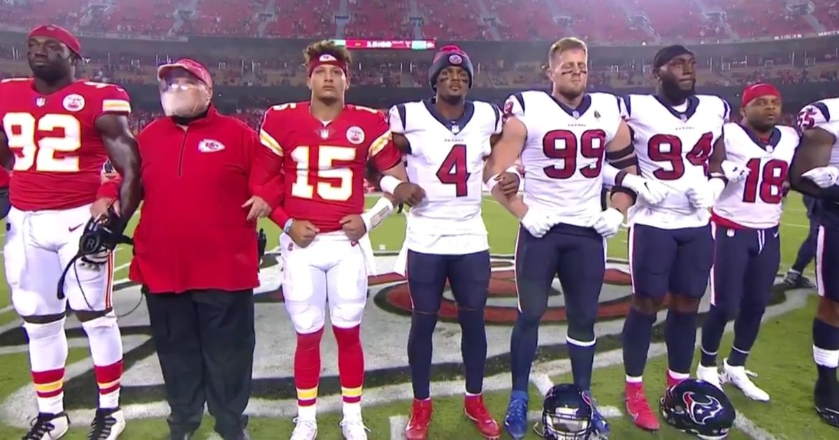 NFL players and coaches from the Houston Texans and Kansas City Chiefs link arms before the opening game of the 2020-2021 NFL season.