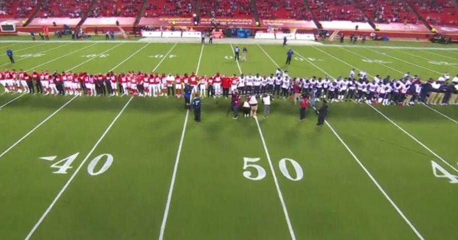 """Players and coaches from the Houston Texans and Kansas City Chiefs gather midfield for a """"moment of silence"""" before the first game of the 2020-2021 NFL season."""