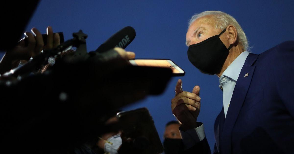 Democratic presidential nominee Joe Biden talks with journalists before departing the Detroit metro area on Sept. 9, 2020, in Romulus, Michigan.