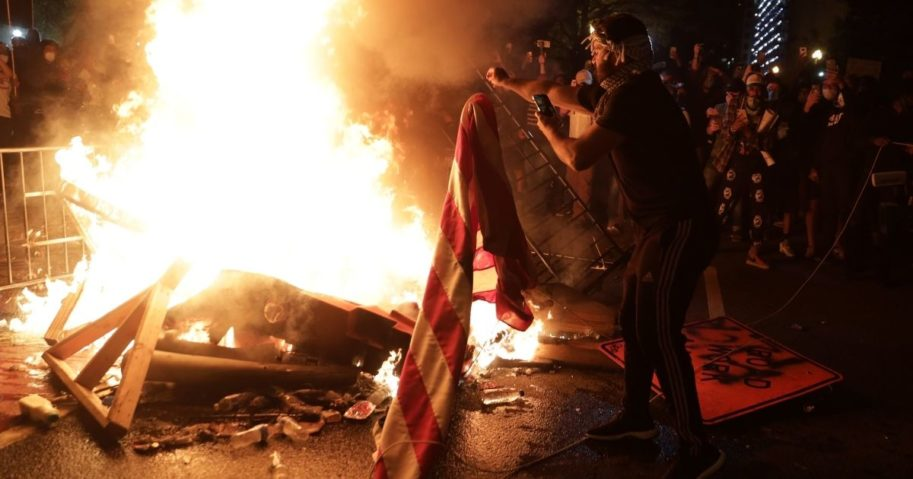 Demonstrators set a fire and burn an American flag during a protest near the White House on May 31, 2020, in Washington, D.C.