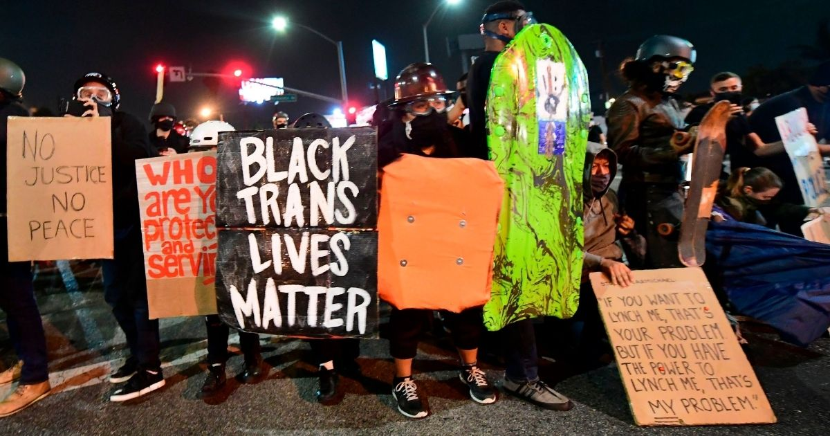 People hold placards and shields as they prepare before being dispersed by sheriff's deputies on Sept. 8, 2020, in Los Angeles.