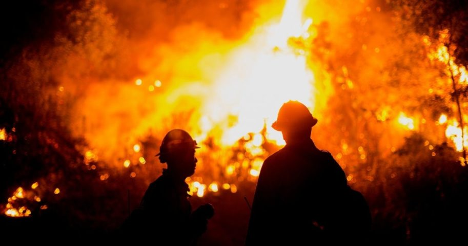 Firefighters watch the Bobcat Fire burning on hillsides near Monrovia Canyon Park in Monrovia, California, on Sept. 15, 2020.