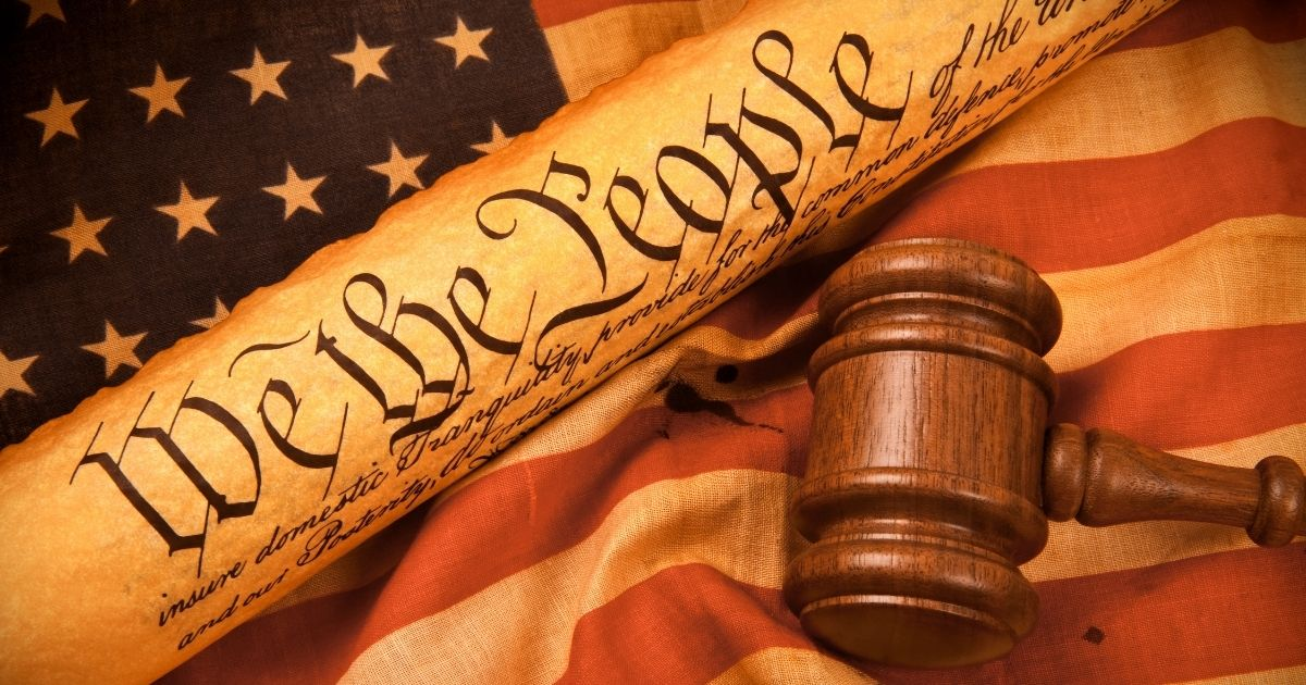 A stock image of the Constitution against an American flag background is pictured above.