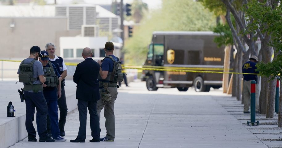 Federal law enforcement personnel stand outside the Sandra Day O'Connor Federal Courthouse on Sept. 15, 2020, in Phoenix. A drive-by shooting wounded a federal court security officer outside the courthouse in downtown Phoenix.