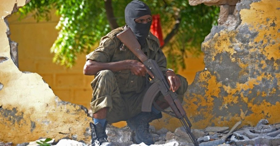 A Somali soldier stands guard at a site where al-Shabab militants carried out a suicide attack against a military intelligence base in Mogadishu on June 21, 2015.