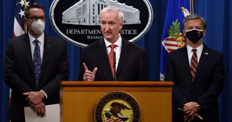 Deputy Attorney General Jeffrey A. Rosen speaks as FBI Director Christopher Wray, right, and Immigration and Customs Enforcement Deputy Director Derek Benner, left, look on at a news conference at the Justice Department on Sept. 22, 2020, in Washington, D.C. The officials reported that 179 people were arrested and more than $6.5 million was seized in a worldwide crackdown on opioid trafficking on the dark net.