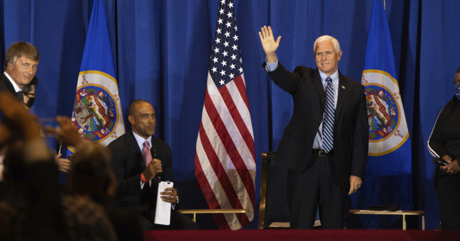 """Vice President Mike Pence waves to an audience as he arrives at a """"Cops for Trump"""" event at Minneapolis-St. Paul International Airport on Sept. 24, 2020."""