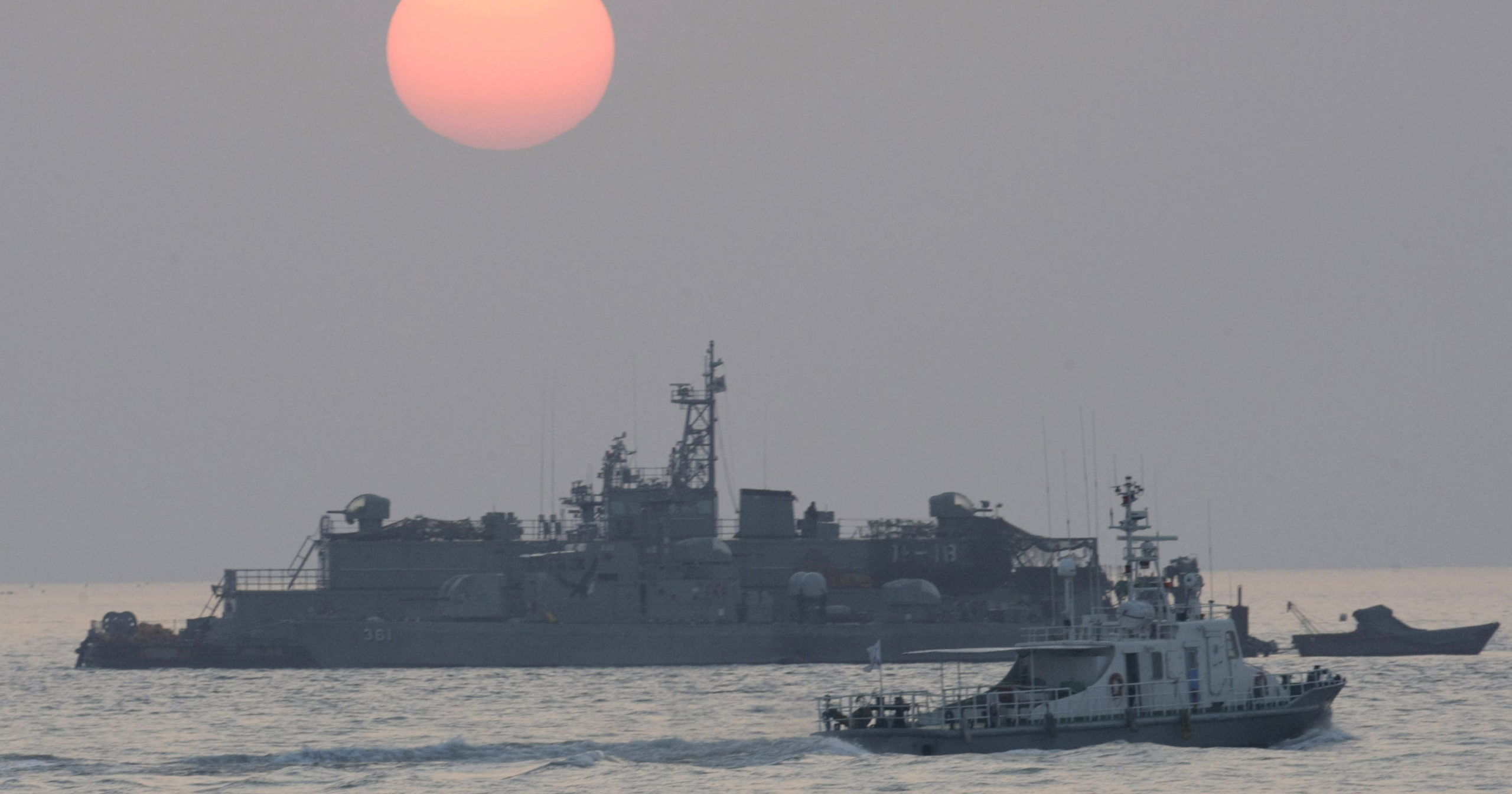 In this Dec. 22, 2010, file photo, a government ship sails past the South Korean Navy's floating base as the sun rises near Yeonpyeong island, South Korea.