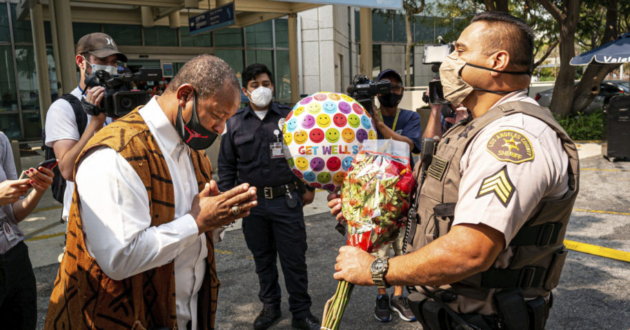 Najee Ali of Project Islamic Hope presents Sgt. Larry Villareal of the Los Angeles County Sheriff's Department flowers for deputies recovering at St. Francis Medical Center in Lynwood, California, on Sept. 14, 2020. The two deputies were shot Sept. 12 while in their patrol vehicle in an ambush attack.