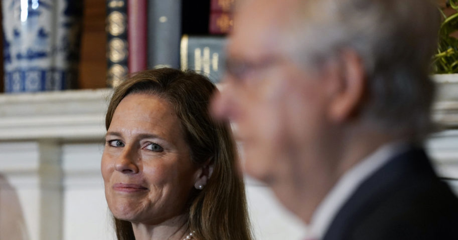 Supreme Court nominee Judge Amy Coney Barrett looks over to Senate Majority Leader Mitch McConnell of Kentucky as they meet on Capitol Hill in Washington on Sept. 29, 2020.