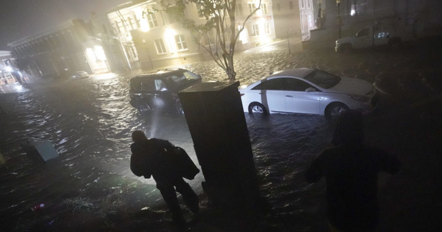 People use flashlights as they walk on flooded streets on Sept. 16, 2020, in Pensacola, Florida. Hurricane Sally made landfall near Gulf Shores, Alabama, as a Category 2 storm, dumping torrential rain that forecasters said would cause dangerous flooding from the Florida Panhandle to Mississippi and well inland in the days ahead.