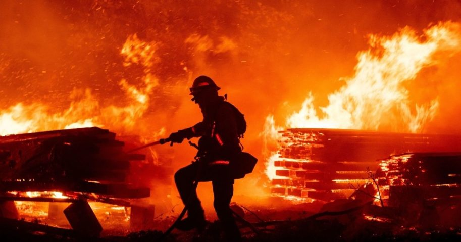 A firefighter douses flames in the Cascadel Woods area of unincorporated Madera County, California, on Sept. 7, 2020.