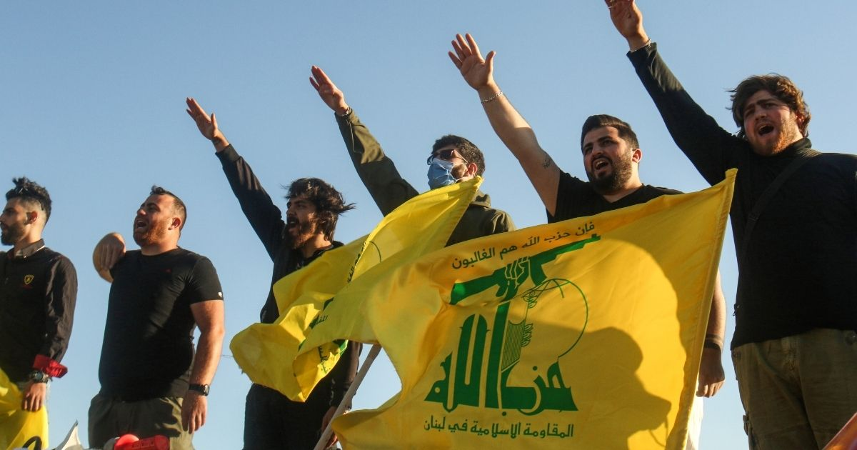 Supporters of the Shiite movement Hezbollah perform a salute in southern Lebanese on the border with Israel on May 25, 2020.