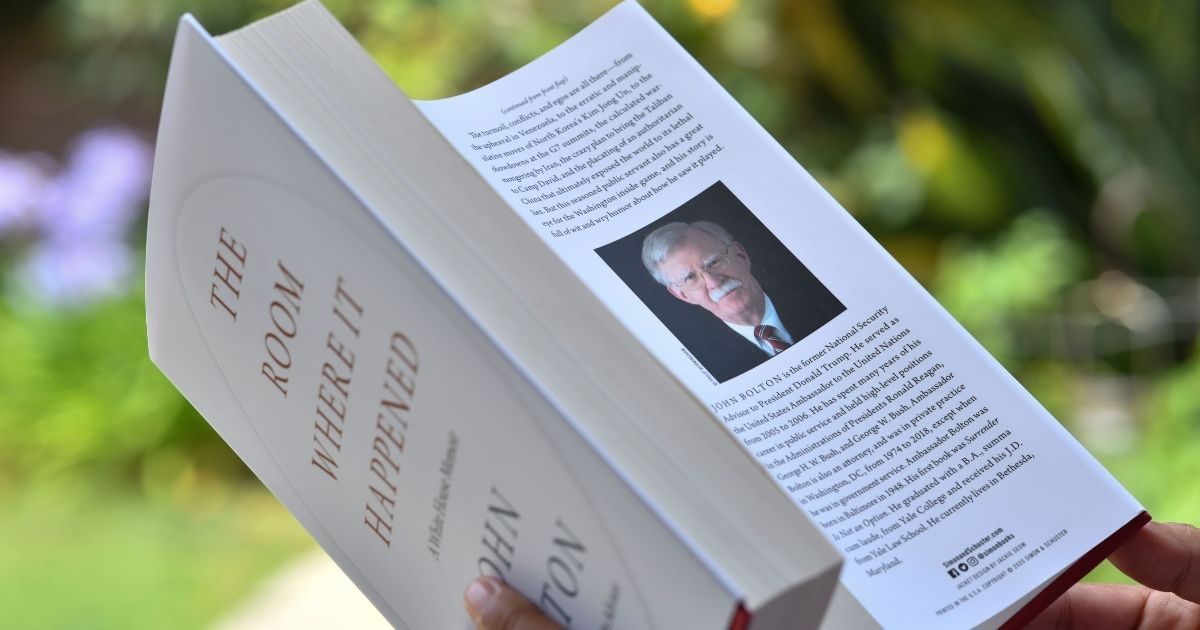 """This photo taken on June 23, 2020, in Glendale, California, shows a woman reading John Bolton's book, """"The Room Where it Happened,"""" on the day of its release in Los Angeles."""