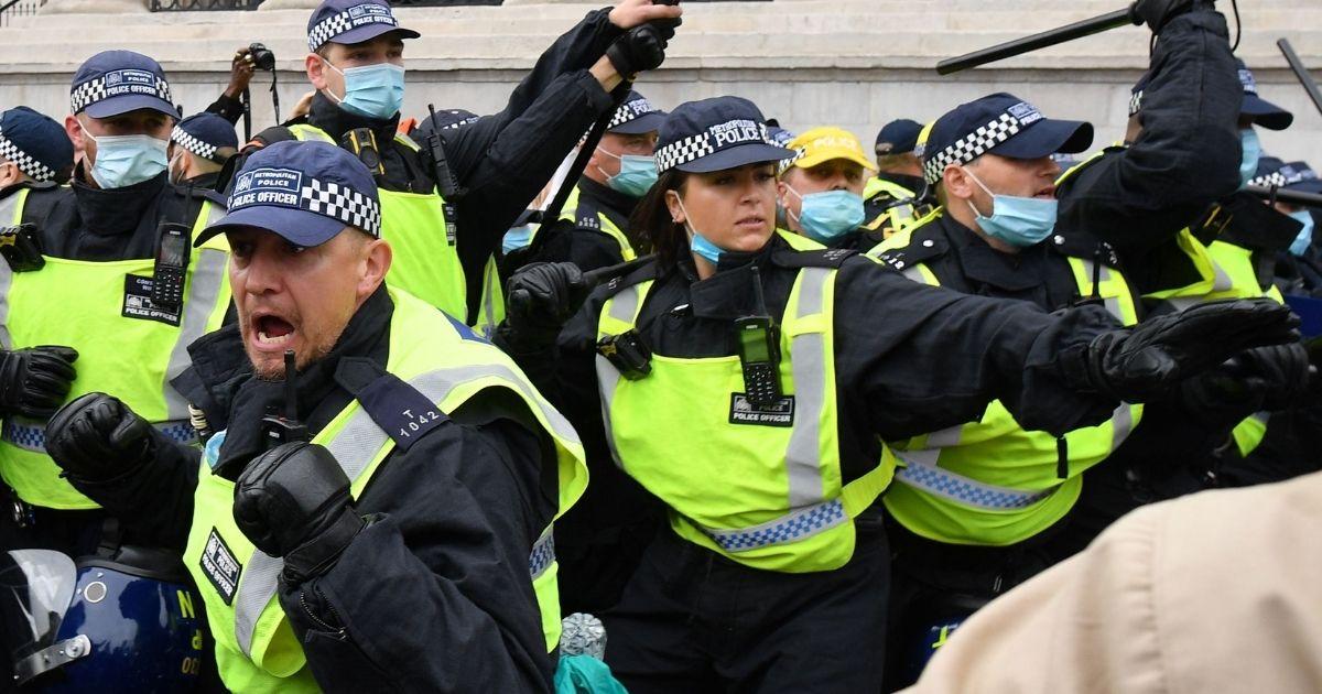 Police move in to disperse protesters in Trafalgar Square in London on Sept. 26, 2020.