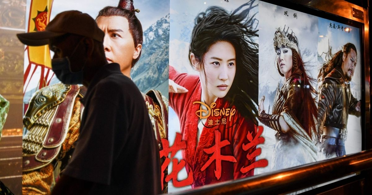 """A man walks past a poster for the movie """"Mulan"""" at a bus stop in Beijing on Sept. 10, 2020. Disney's """"Mulan"""" remake is facing boycott calls after it emerged that some of the blockbuster's scenes were filmed in Xinjiang, China, where widespread rights abuses against the region's Muslim population have been widely documented."""