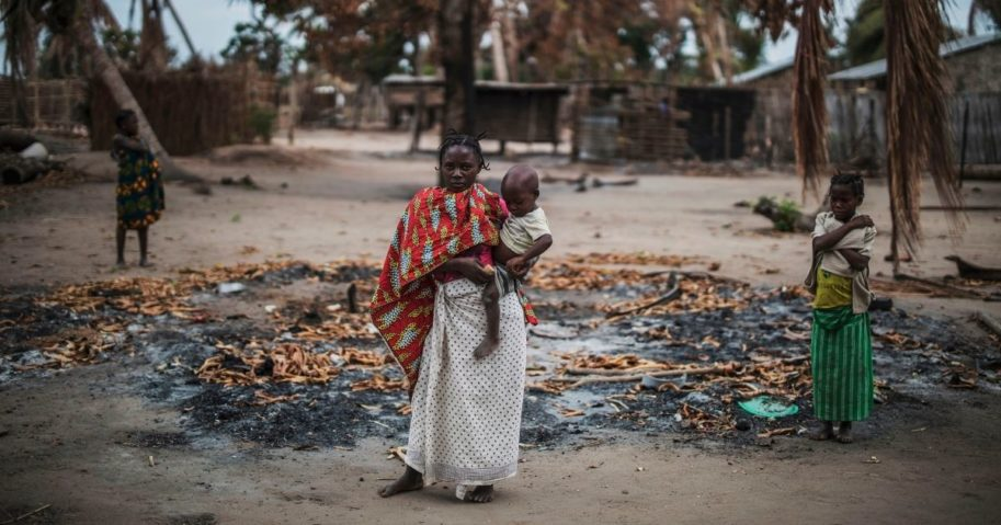 A woman holds her child in a burned area in a village after an attack by an Islamist group in the Macomia province of Mozambique on Aug. 24, 2019.
