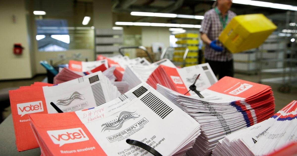 Vote-by-mail ballots for the presidential primary are stacked on a table in Renton, Washington, on March 10, 2020.