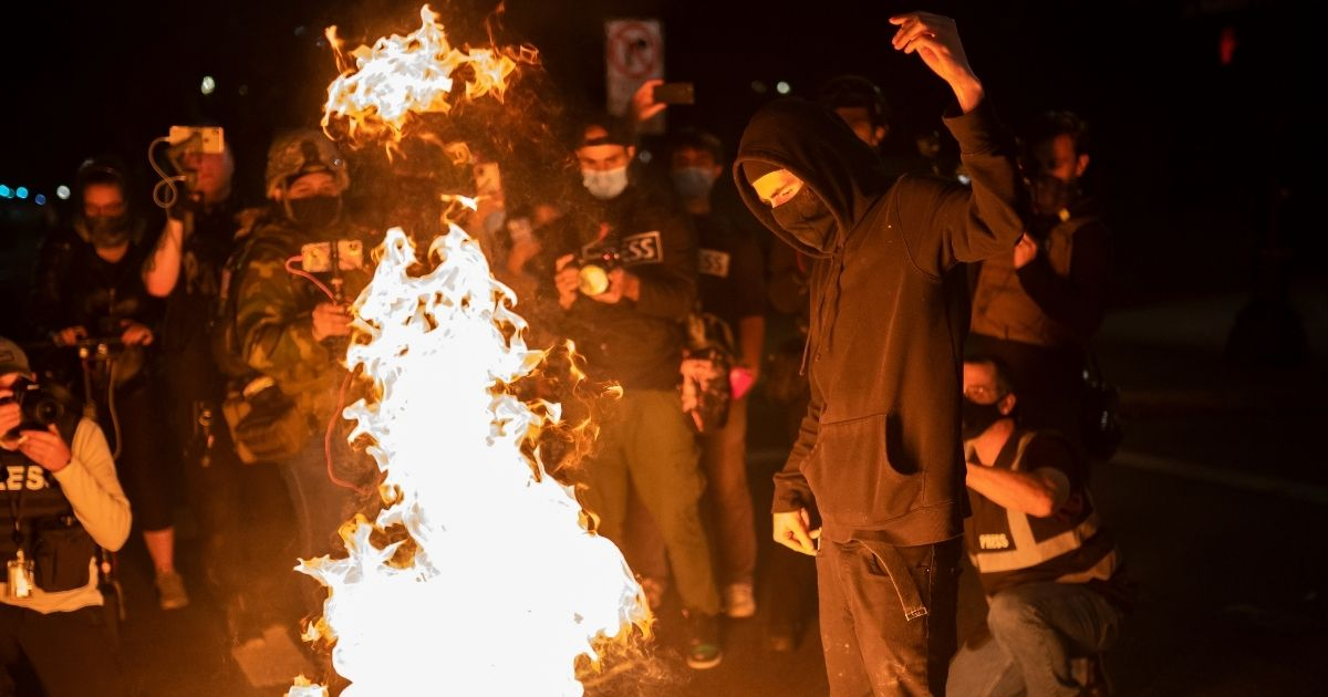 A protester burns an American flag on Sept. 26, 2020, in Portland, Oregon.